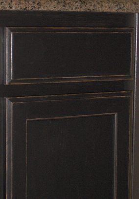 Detail of kitchen cabinets painted satin black then antiqued and